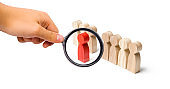 Magnifying glass is looking at the red figure of a man comes out of the line of people. Talent, leader, professional. improvement in work, the universal recognition of efficiency and leadership