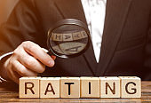 Wooden blocks with the word Rating and a magnifying glass in the hands of a businessman. The concept of studying the rating of the hotel and restaurant. Evaluation of the critic. Quality review.
