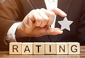 Businessman holds one star above the wooden blocks with the word Rating. Concept of negative feedback. Low quality and service serving. Evaluation of the critic. Hotel or restaurant rating