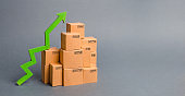 Lots of cardboard boxes and a green arrow up. growth rate of production goods, raise economic indicators. Increasing consumer demand. exports and imports. sales rise. High throughput, logistics.