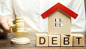 Wooden blocks with the word Debt and a miniature house with a judge's hammer. Confiscation of property for failure to pay the debt. The withdrawal of housing. Moratorium. Criminal penalty