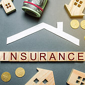 Table with wooden houses, calculator, coins, magnifying glass with the word Insurance on wooden blocks. The concept of property insurance and housing. Accumulation of money