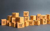 Many cardboard boxeswith drawing of shopping carts. products, goods, Warehouse, stock. commerce and retail. E-commerce, sale of goods through online trading platform. Freight shipping, deliver
