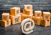 Wooden email symbol stands near the cardboard boxes. Concept of online trading and e-commerce. Distribution and retail. Shopping. Internet advertising. Marketing, targeting. Production of goods