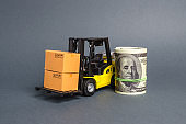 A forklift truck carries cardboard boxes and dollar roll. Transport company. Performance efficient. Trade and production of products and goods, balance import export. development of the global economy