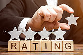 Businessman puts the fifth star above the word Rating on wooden blocks. The concept of the high rating of hotels and restaurants. The evaluation of critics and visitors. Quality level, good service