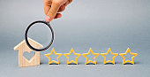 Five stars and a wooden house on a gray background. The concept of the best housing, luxury apartments VIP class. The best service and universal recognition, a high evaluation. Success. Feedback