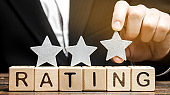 Businessman puts the third star above the word Rating on wooden blocks. The concept of quality of service. Hotel or restaurant rating. Evaluation of critics and visitors. Good quality. Feedback. Three