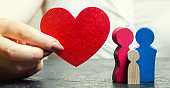 A woman holds in her hands a red heart near a miniature family. Concept of life and health insurance. Insurance agent services. Protection and security. Protect property. Female