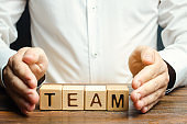Businessman protects wooden blocks with the word Team. Care for employees. Security and safety in a business team. Human resources. A responsibility. Social protection. Life insurance.