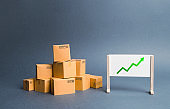 A pile of cardboard boxes and stand with green up arrow. Price increase. The growth rate of production. Increasing consumer demand. exports and imports rise. Growth of income from the sale of goods.