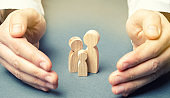 Insurance agent holds hands near the family. The concept of insurance of family life and property. Family care and helping hand concept. Health insurance. Health care. Security and Property Protection