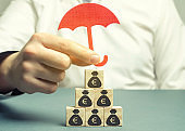 Insurance agent protects wooden blocks with the image of the euro. Savings protection. Keeping money safe. Investment and capital insurance. The risk of doing business. Corruption losses.