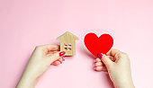 A girl holds a house and heart in her hands. The concept of affordable housing. A dream is to buy a house. Accumulation on the apartment. Property rental. Sale and mortgage real estate. Sweet Home