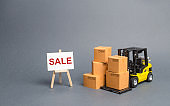 Yellow Forklift truck with cardboard boxes and stand with the word sale. sale of goods, big discounts on goods of the outgoing season. commodity exchange with other countries. Attracting buyers