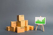 Pile of cardboard boxes and a stand with information chart. rate growth of production of goods and products, increasing economic indicators. Increasing consumer demand, exports or imports.