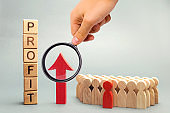 Wooden blocks with the word profit and the graph up stands near the team. Concept of business success, financial growth and wealth. Increase profits and investment fund. Economic boom High performance
