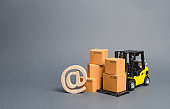 Yellow Forklift truck and cardboard boxes and email symbol commercial AT. E-commerce. sales of goods through online trading platforms. shopping online. development of Internet network trade.