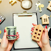 A girl holds in his hands a dollars and a miniature house. The concept of risk assessment for the purchase of real estate. Attracting investment in property. Realtor services. Sale or rental apartment