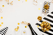 Christmas party composition. Gifts, hats, champagne bottle black and gold decorations on white background