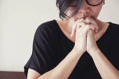 Asian middle aged woman wear glasses praying with hands together in the morning