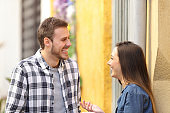 Happy couple talking and laughing in the street