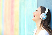 Happy girl listening to music on a colorful wall