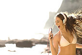 Happy tourist in bikini listens to music and sings songs