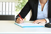 Businesswoman signing a contract on a desktop at office