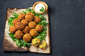 Vegetarian chickpeas falafel balls on wooden rustic board. Traditional arabian food.