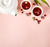 Herbal tea with roses on pink background