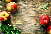 Fresh apples with leaves on wooden background