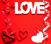 Word Love and red gift box at red background, Valentine Day concept