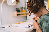 little girl draws with color markers in her desk