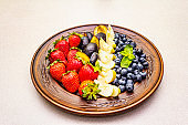 Raw fruits berries platter, apple, strawberry, blueberry, plum, mint