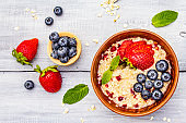 Healthy breakfast vegetarian (vegan) concept. Oatmeal with fresh berries and mint