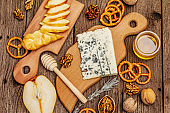Cheese plate antipasti with smoked and blue cheese, crackers, honey, walnuts and ripe pear. Traditional snack recipe idea. Wooden boards background