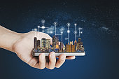 Smart city, building technology and mobile application technology. Hand holding mobile smart phone with buildings hologram and application programming interface technology