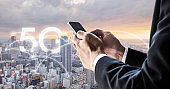 Internet networking and wireless technology. Businessman using mobile smart phone with city view in sunset, and 5G internet networking