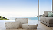 Sea view living room of luxury summer beach house with sofa and coffee table. Empty white marble podiums in studio or showroom.