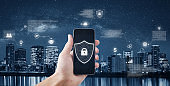 Mobile phone applications data security and internet safety technology. Businessman unlocking mobile smart phone with city background