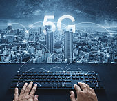 5G internet networking technology, Hand typing on computer keyboard with city and 5g internet connection