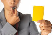 Business woman holding yellow card and blowing a whistle