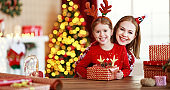 happy family mother and child pack Christmas gifts at home near Christmas tree