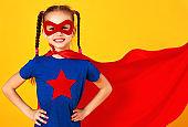 concept of child superhero costume on yellow background