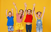 group of cheerful happy children on colored yellow background