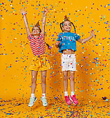 happy children girls twins on holidays  jumping in multicolored confetti on yellow
