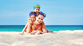 Happy family mother and chidren in masks on beach in summer