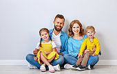 happy family mother father and children daughter and son  near an   grey blank wall
