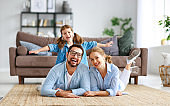happy family mother father and child daughter at home on couch